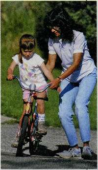 девочка учится кататься на велосипеде