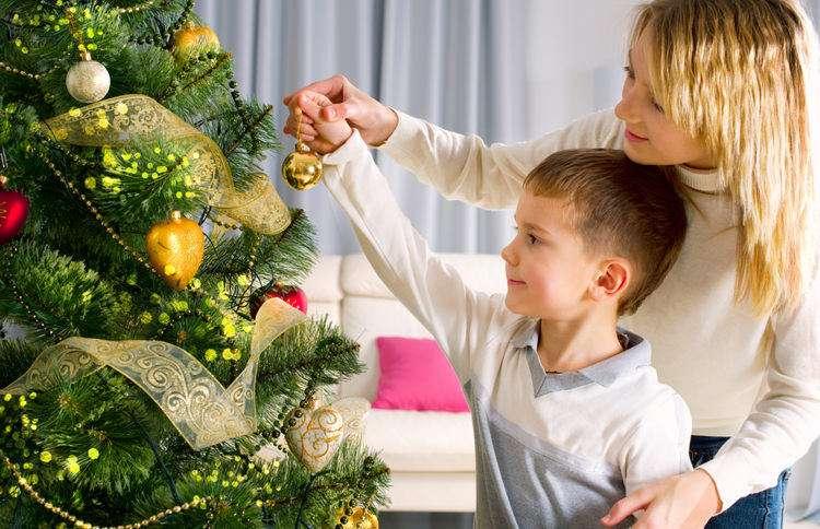 мама и дочь наряжают новогоднюю елку
