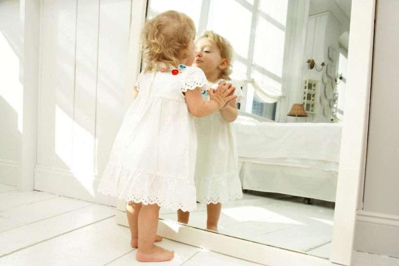 Маленькая девочка, ребенок смотрит в зеркало