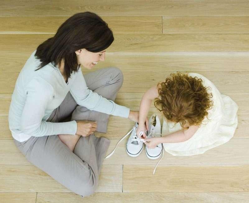 Мама учить ребенка завязывать шнурки
