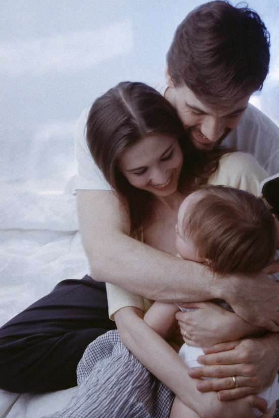 Родители обнимают ребенка