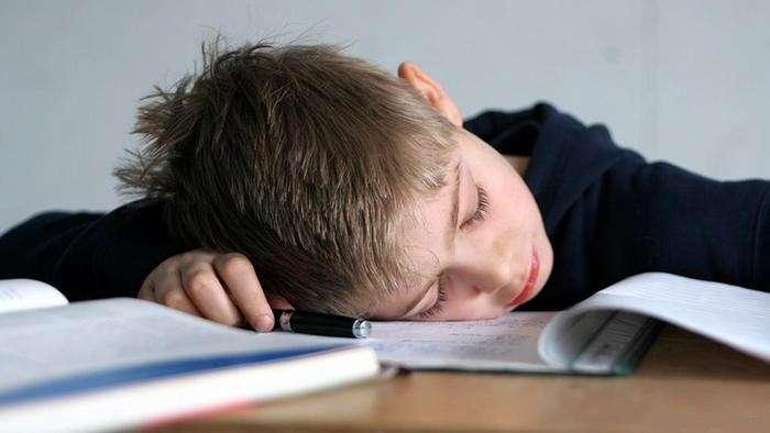 ребенок спит за учебниками