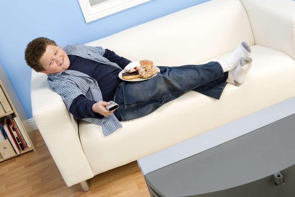 Гиподинамия - ребенок ест и смотрит телевизор лежа на диване