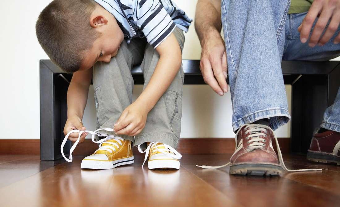 учится шнуровать ботинки
