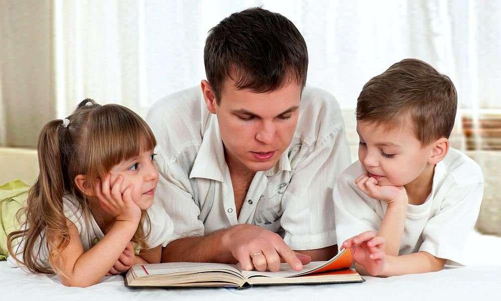 Отец читает книгу с детьми
