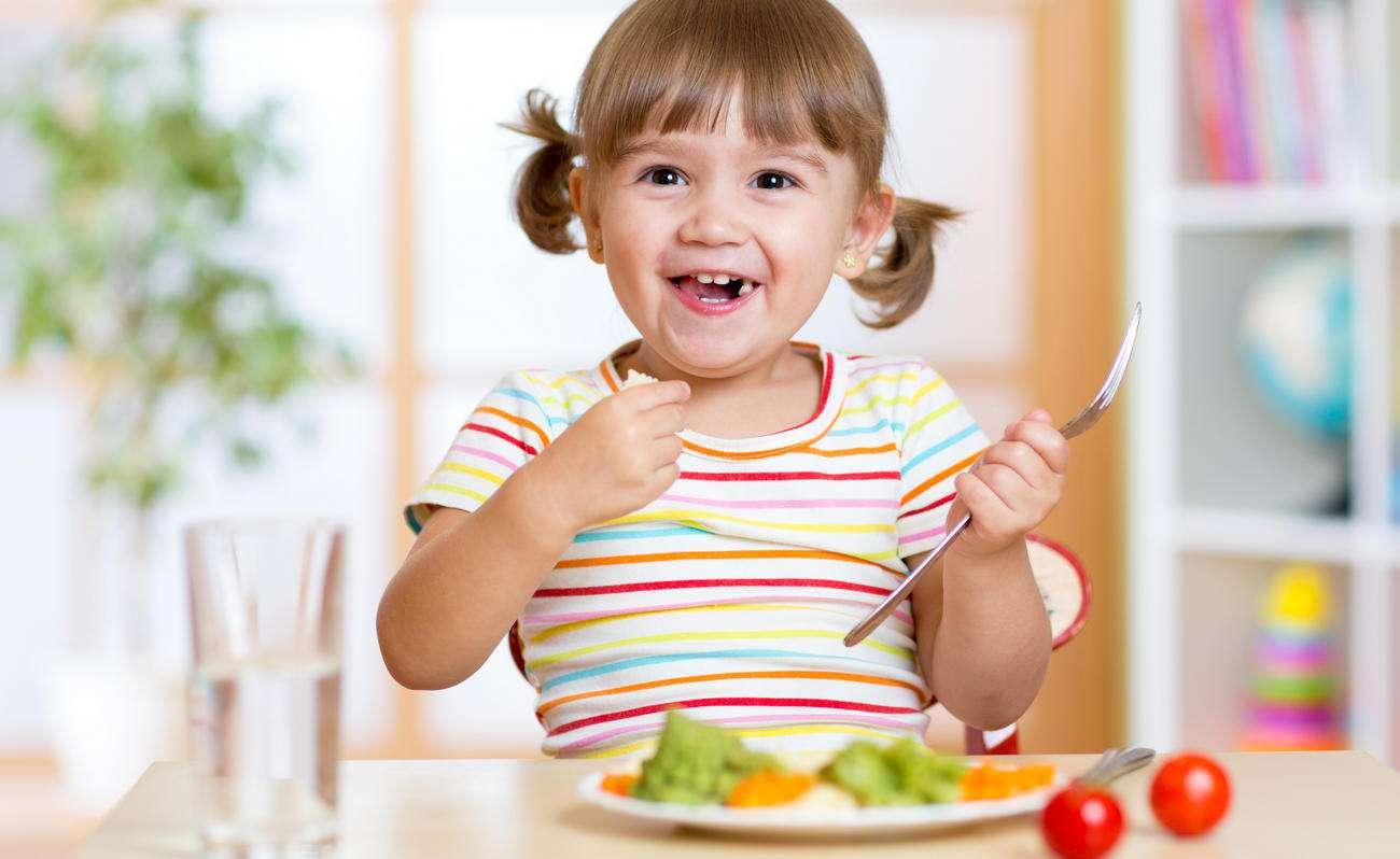 Девочка есть овощи с аппетитом