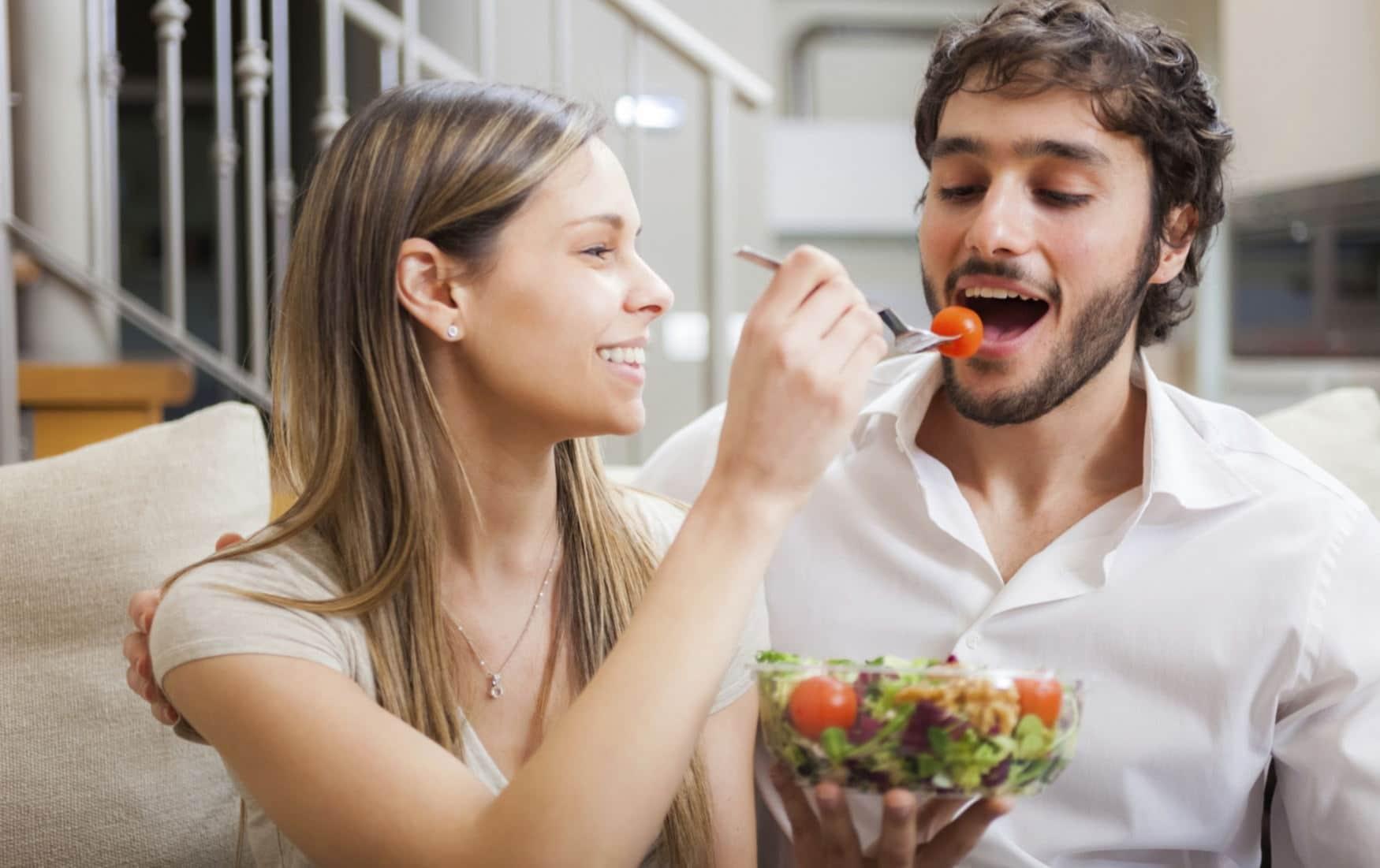 Девушка кормит парня салатом
